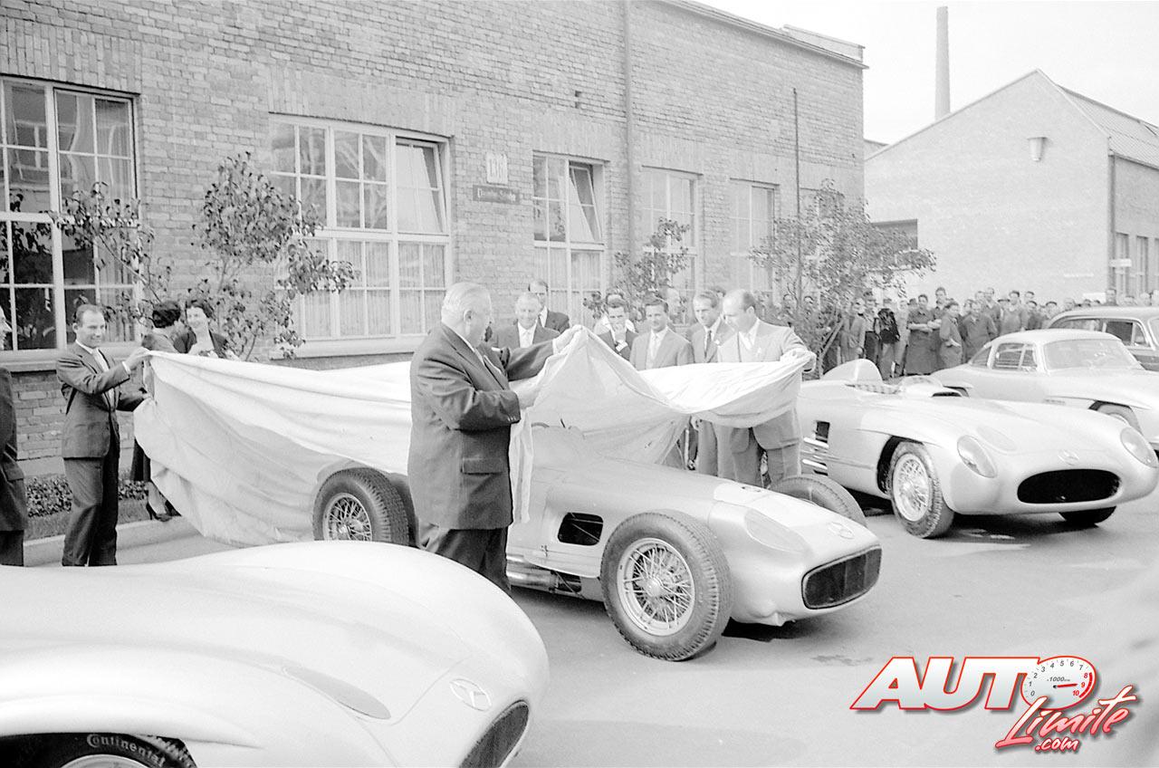 """Alfred Neubauer (Jefe del Equipo Mercedes) y los dos pilotos oficiales (Juan Manuel Fangio y Stirling Moss) cubriendo los Mercedes """"Flecha de Plata"""" con los que ganaron los Mundial de Fórmula 1 y de Turismos en la temporada 1955. Durante las 24 Horas de Le Mans de dicho año, uno de los coches oficiales de Mercedes sufrió el peor accidente de la Historia del automovilismo y Mercedes decidió retirarse de la competición al finalizar la temporada en señal de duelo."""