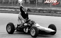 """Al finalizar el Gran Premio de Italia de 1963, el patrón del equipo Lotus, Colin Chapman, paseo a """"lomos"""" del Lotus 25 el trofeo de vencedor obtenido por Jim Clark en el circuito de Monza. Por si fuera poco, sobre el monoplaza se subió también Mike Spence, el segundo piloto del equipo Lotus, que había tenido que abandonar por una avería a lo largo de la carrera."""